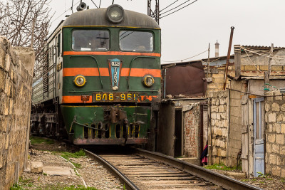 A freight train passing through a narrow alley in Shanghai, Baku, Azerbaijan.